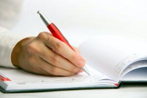 Closeup view of a businesswoman writing in a datebook