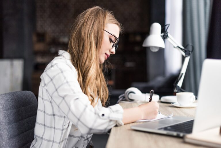 concentrated young woman writing in notebook at workplace