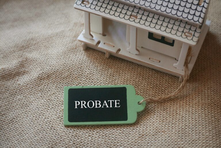 A toy wooden house on a rugs with a wooden tag written with word Probate.