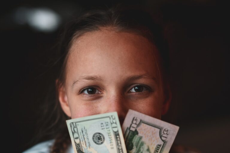 Child holding cash money savings account learning the value of money and not spending