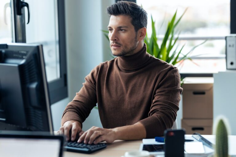 Handsome young entrepreneur working with computer in modern startup office.