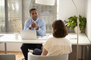Male Financial Advisor In Modern Office Sitting At Desk Meeting Female Client