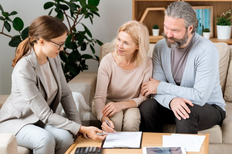 Mature blonde woman listening to real estate agent while going to sign contract