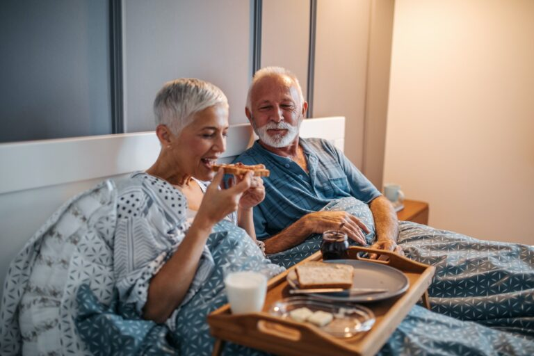 Older man and woman eating in bed