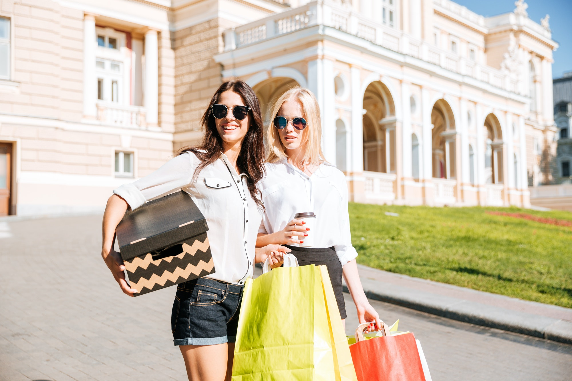 Two attractive girls standing with shopping bags on the street