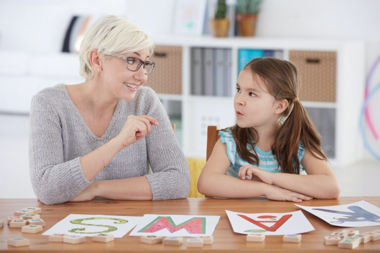 Child studying alphabet with teacher