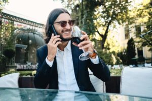 Rich smiling latin man happily talking on cellphone drinking wine resting in restaurant outdoor