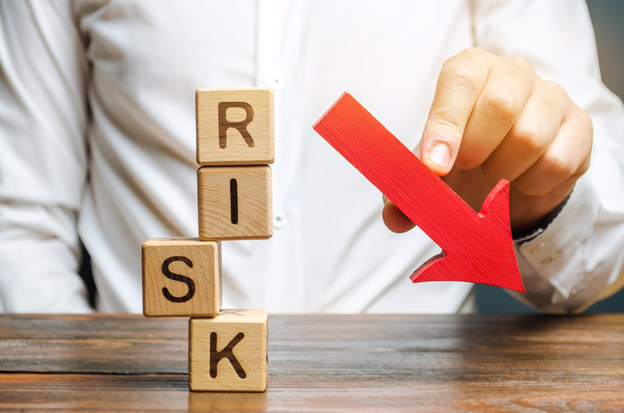 Wooden blocks with the word Risk and a down arrow