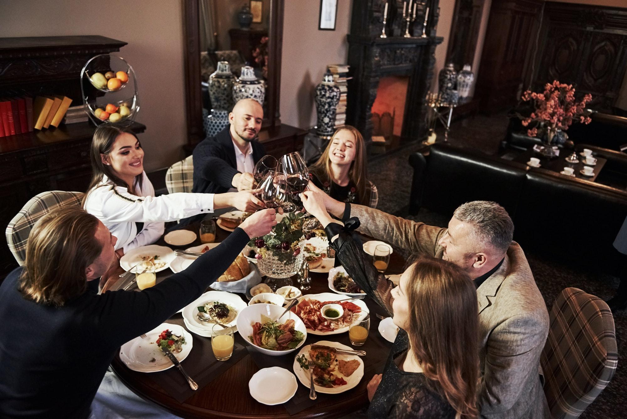 Rich people. Family friends having nice time in beautiful luxury modern restaurant