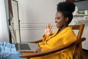 Smiling African American millennial woman sitting in chair talking in video chat on laptop say hello