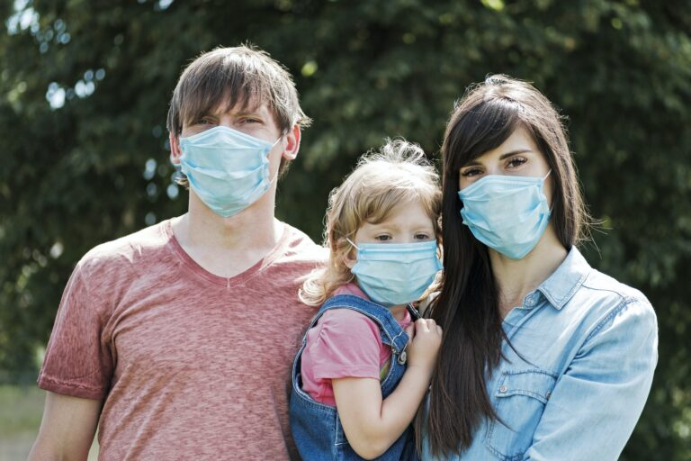 Young family with daughter wearing face masks