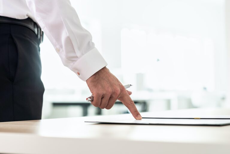 Businessman standing at his office desk pointing to a document