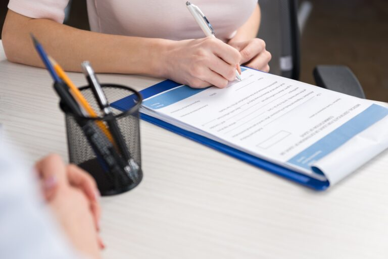 cropped view of patient filling medical form in professional clinic