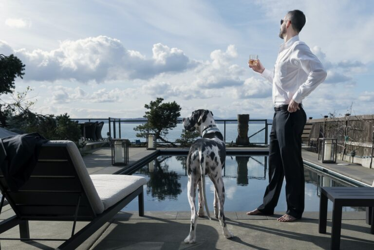 Wealthy man with dog at swimming pool