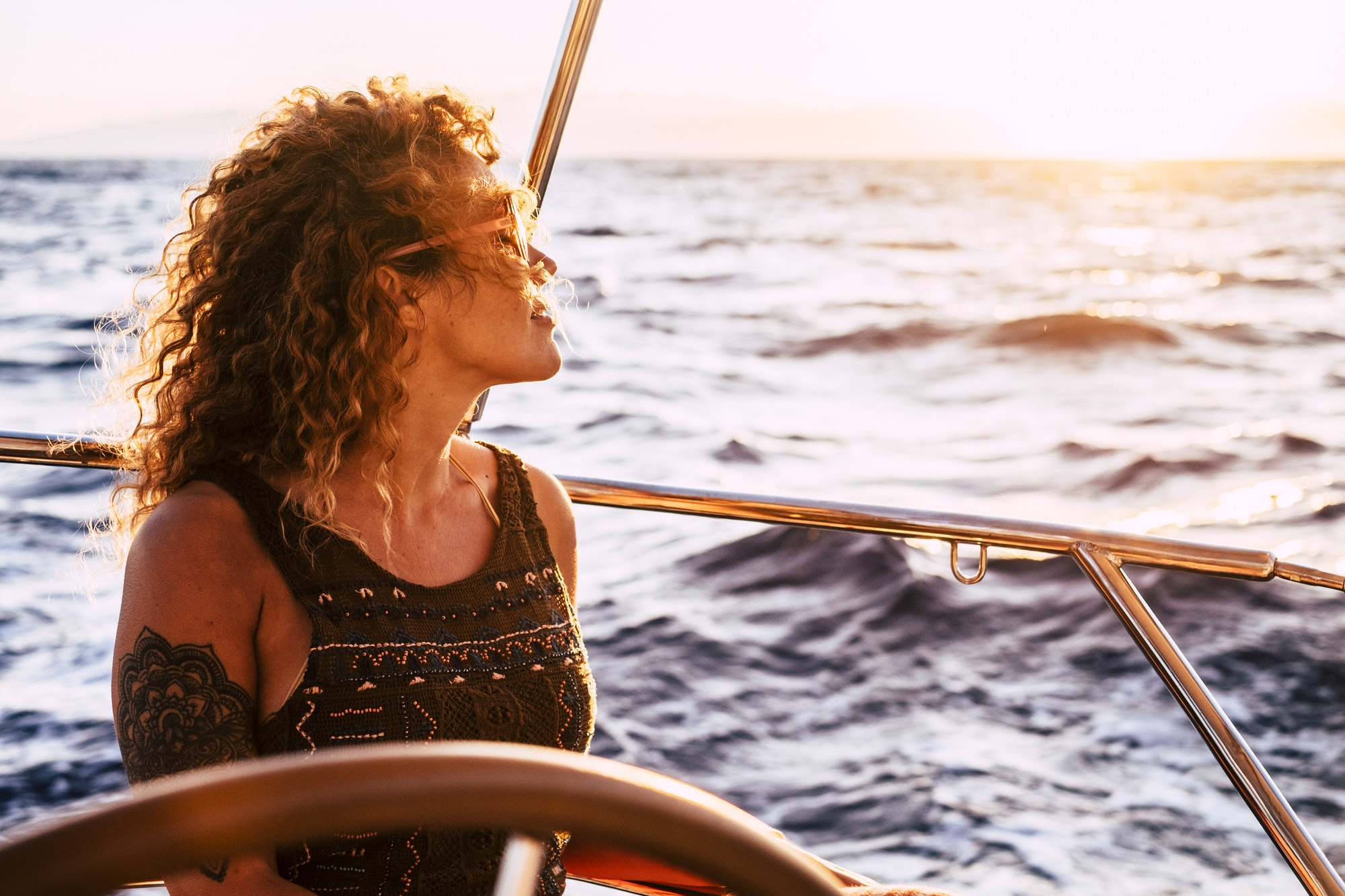 Adult rich woman enjoy luxury lifestyle traveling on sailboat yacht for summer holiday vacation