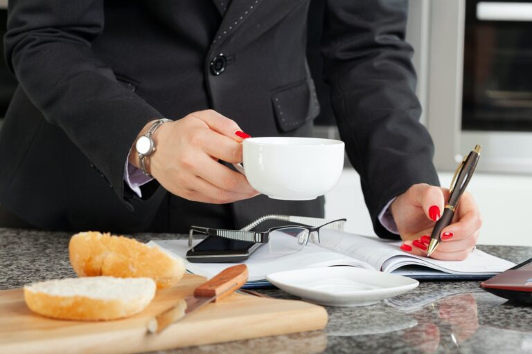 Woman in an elegant jacket holds a cup with coffee over an open calendar at a kitchen counter