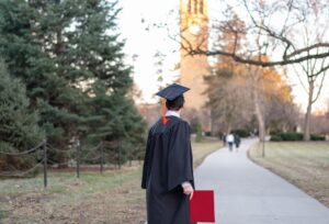 Back view of college graduate in cap and gown holding his diploma